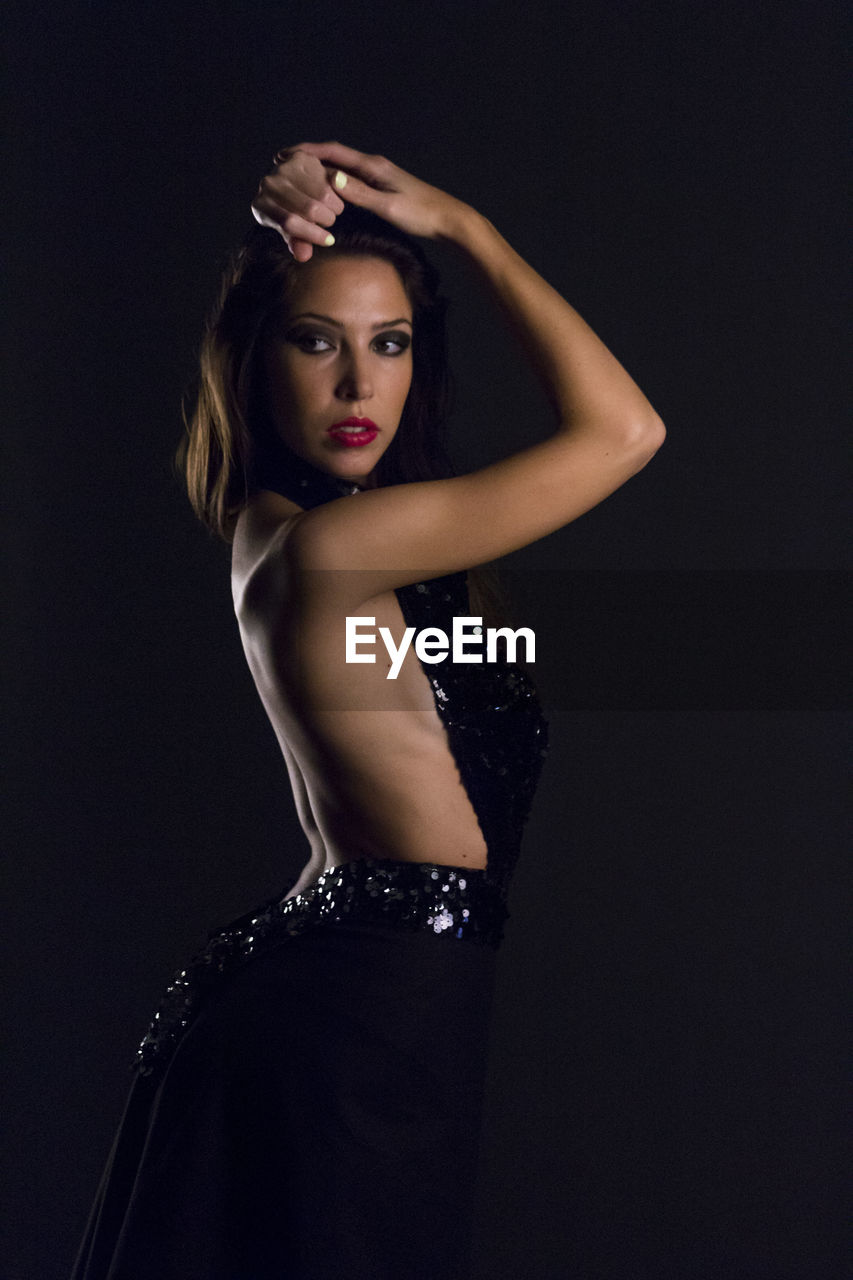 Young woman wearing backless dress while posing against black background