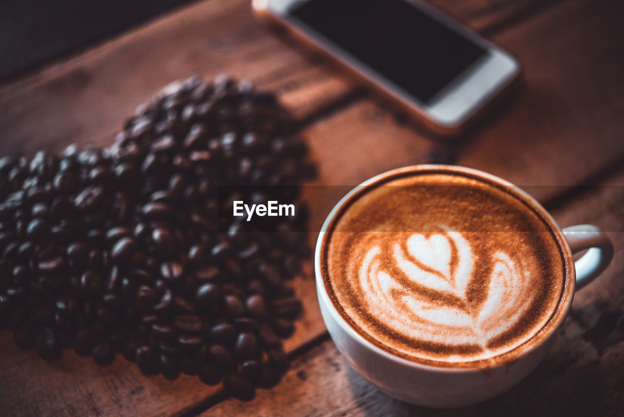 food and drink, coffee, coffee - drink, drink, refreshment, coffee cup, cup, still life, mug, frothy drink, table, cappuccino, froth art, wireless technology, food, hot drink, technology, freshness, high angle view, close-up, no people, crockery, latte, coffee shop