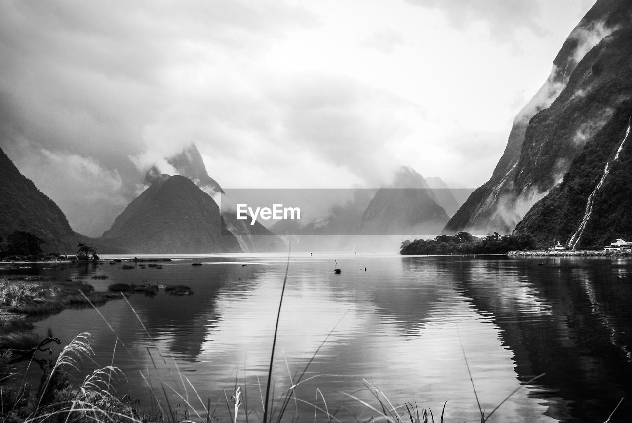 Scenic view of lake and mountains against sky, milford sound