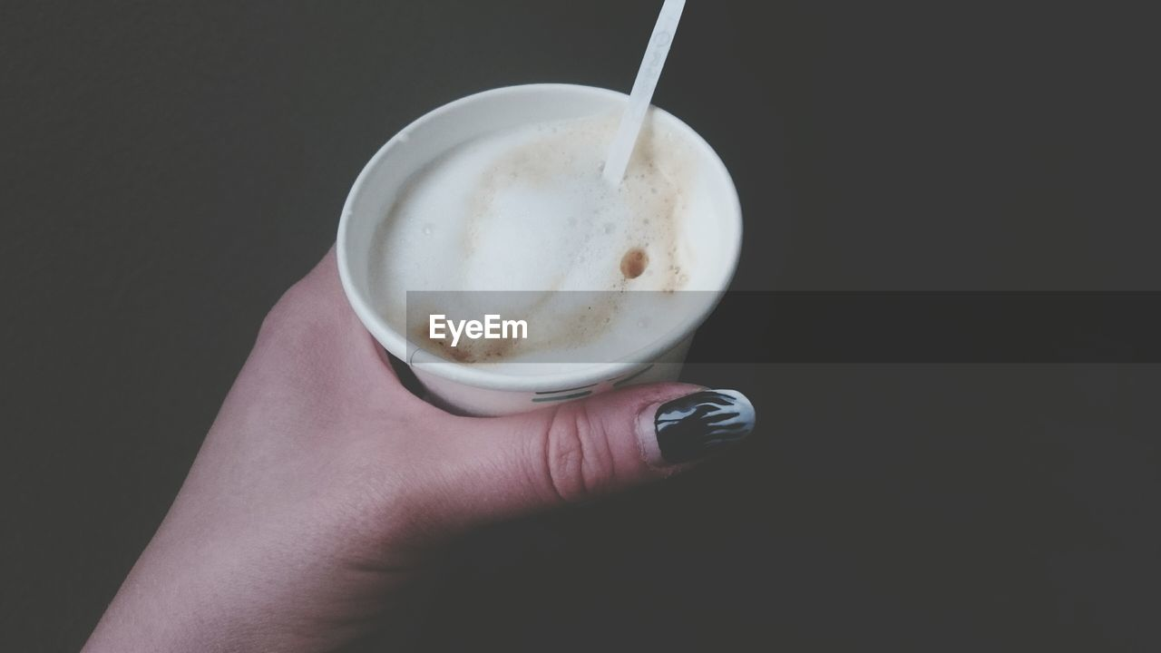human hand, human body part, holding, real people, one person, food and drink, drink, human finger, coffee cup, coffee - drink, personal perspective, refreshment, freshness, frothy drink, close-up, studio shot, lifestyles, food, black background, women, indoors, day, people