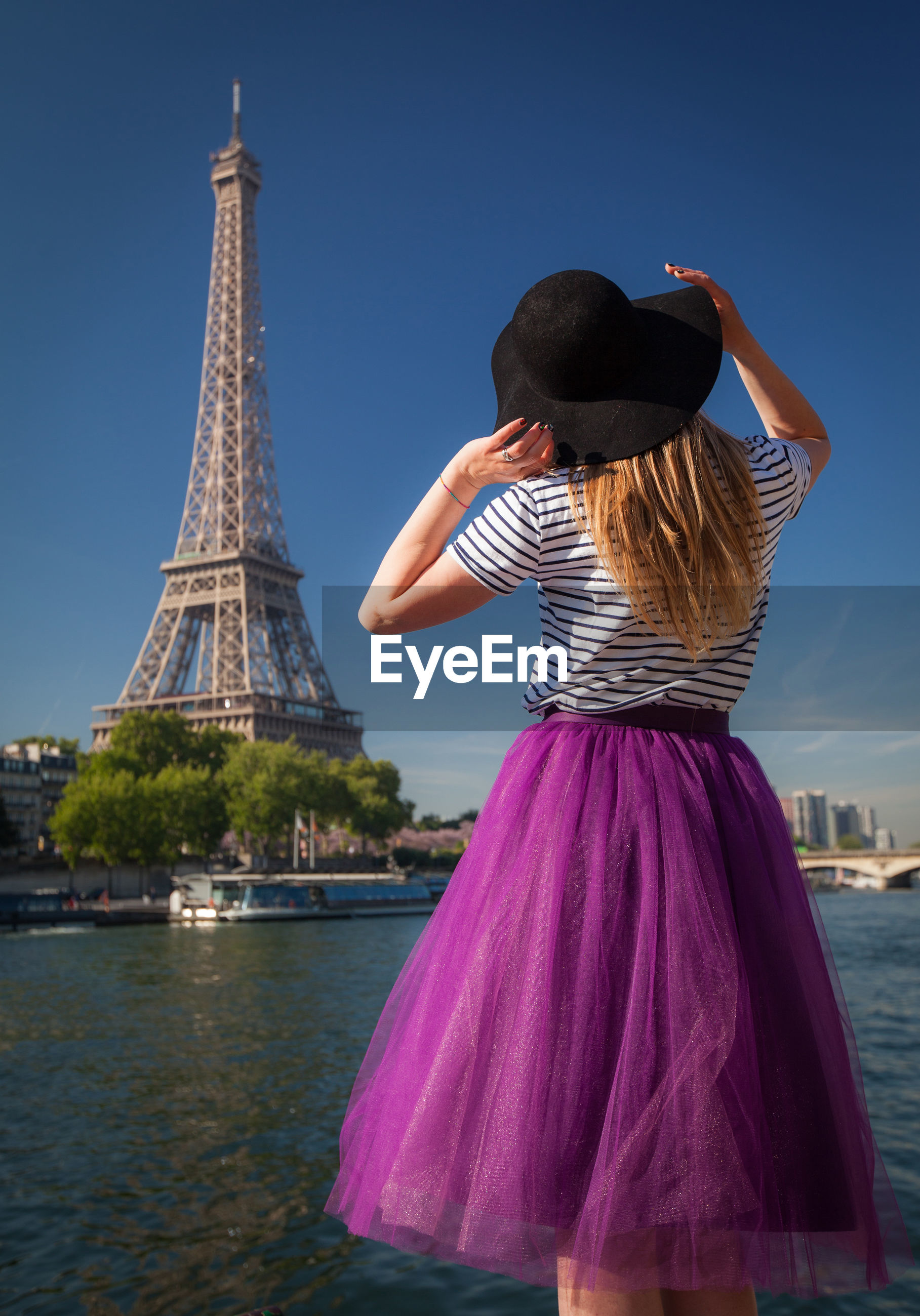 Rear view of woman standing against eiffel tower by river against blue sky
