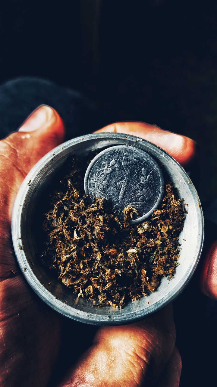 Close-Up Of Hand Holding Marijuana And Coin In Container