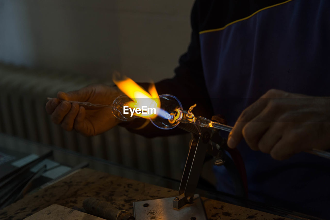 Close-Up Of Hands Making Glass In Factory