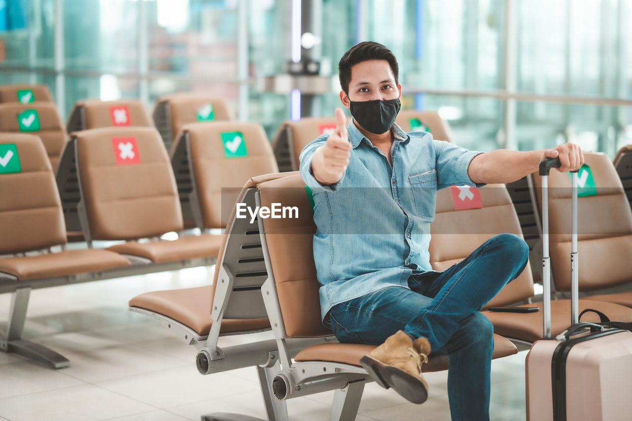 Portrait of mid adult man wearing flu mask gesturing while sitting at airport