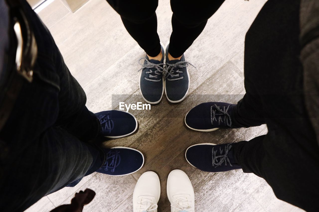 low section, shoe, human leg, real people, body part, human body part, standing, high angle view, group of people, lifestyles, people, men, personal perspective, leisure activity, day, flooring, friendship, togetherness, casual clothing, directly above, outdoors, human foot, jeans
