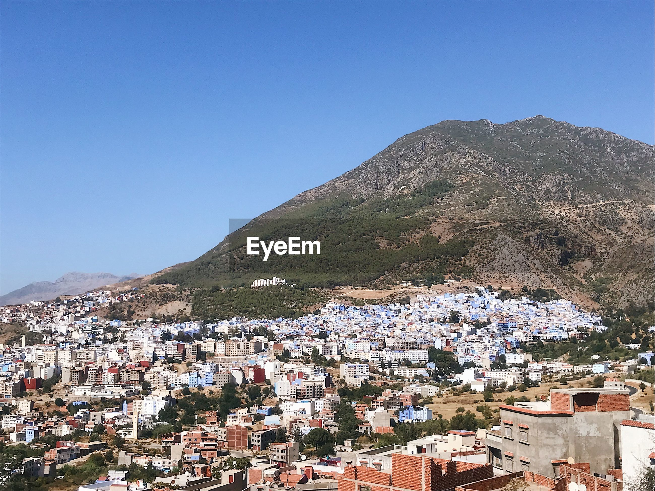 Aerial view of townscape by mountain against clear blue sky