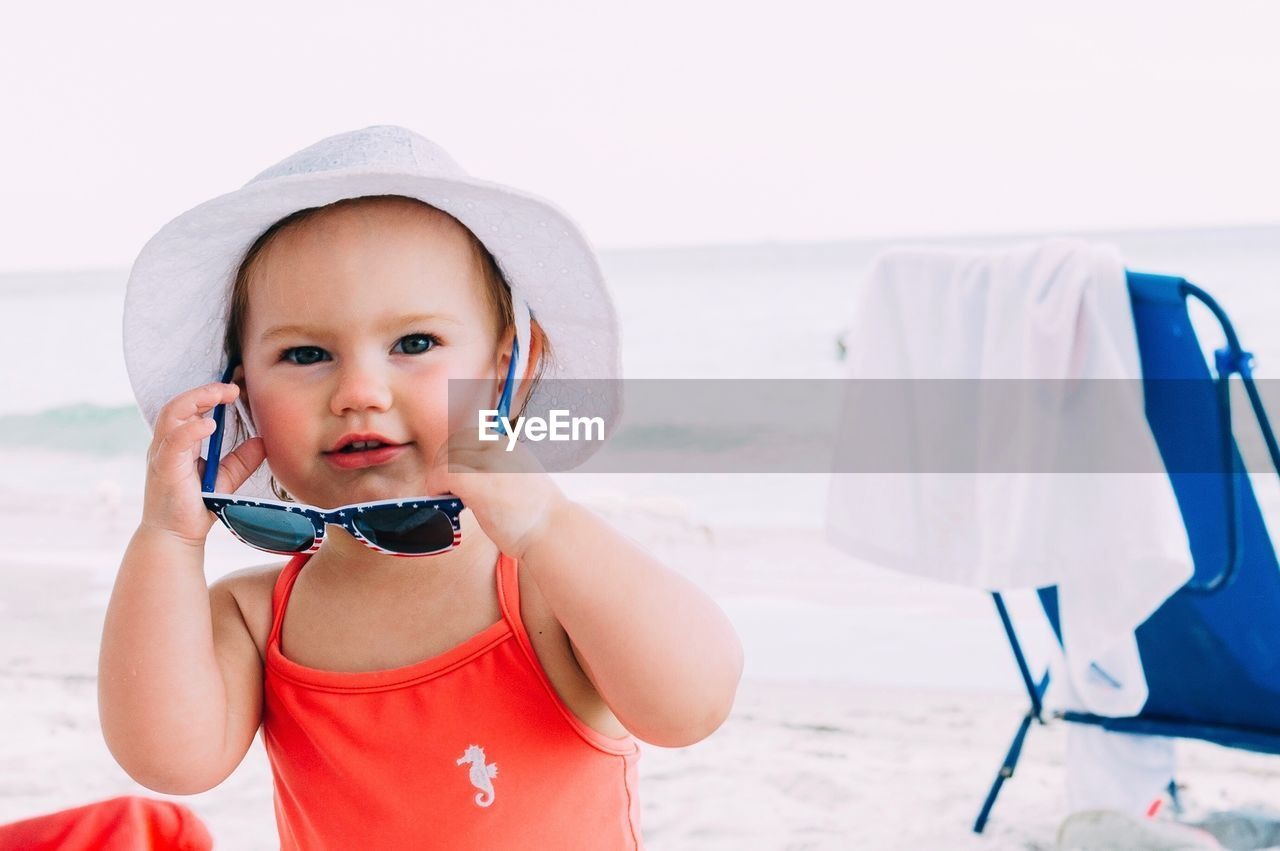 childhood, child, real people, cute, focus on foreground, innocence, one person, front view, portrait, beach, babyhood, lifestyles, land, baby, leisure activity, day, toddler, hat, water