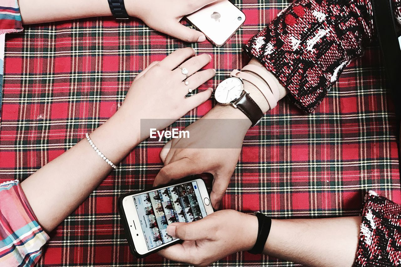 human hand, human body part, real people, holding, togetherness, two people, women, checked pattern, lifestyles, communication, human leg, portable information device, celebration, playing, bonding, indoors, men, red, wireless technology, photographing, technology, friendship, day, adult, people