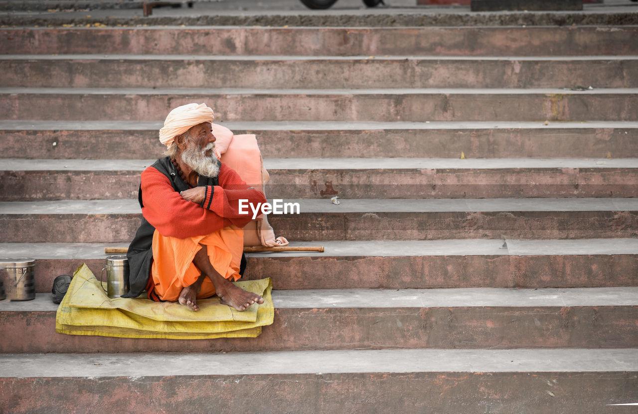 Homeless senior man sitting on steps