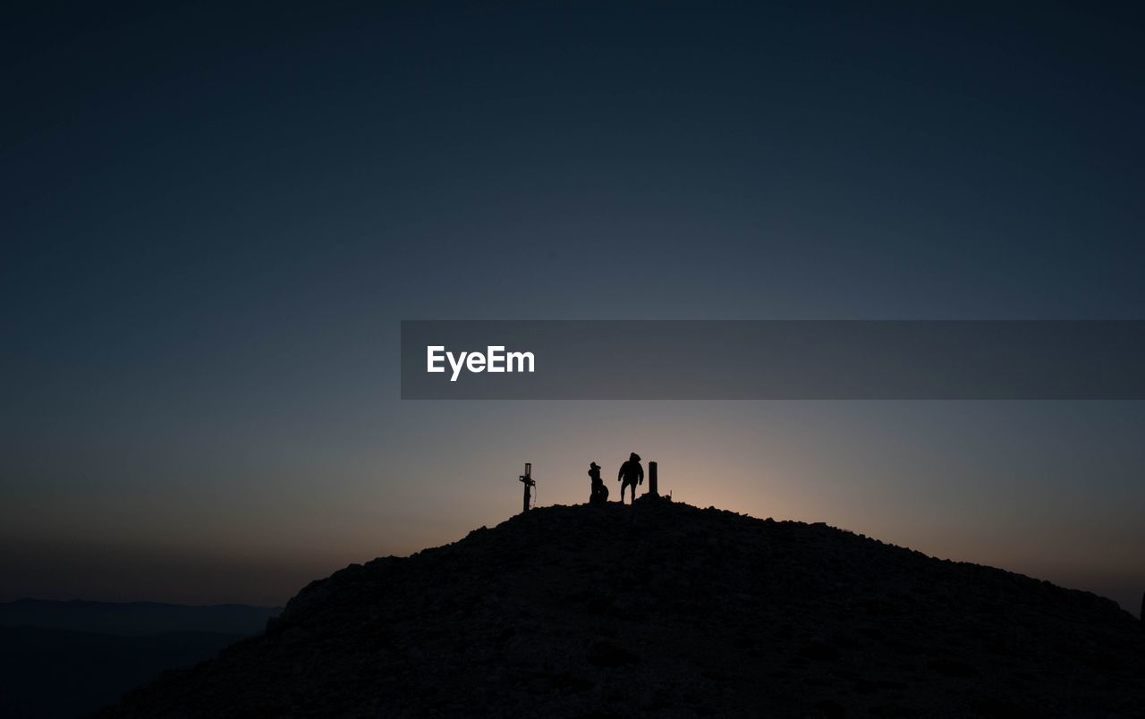 sky, silhouette, leisure activity, copy space, lifestyles, beauty in nature, nature, real people, standing, clear sky, men, togetherness, two people, people, rock, sunset, land, tranquility, tranquil scene, scenics - nature, outdoors