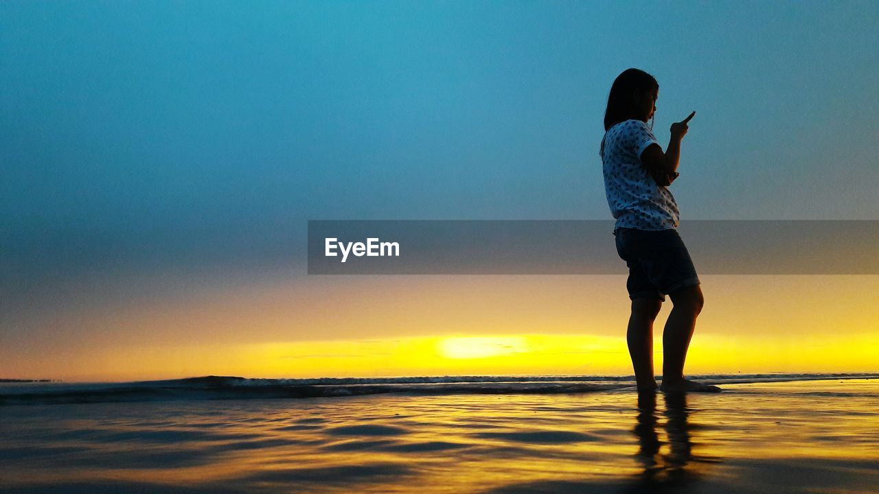 sunset, sea, standing, real people, full length, silhouette, beauty in nature, nature, water, sky, one person, scenics, outdoors, leisure activity, horizon over water, lifestyles, clear sky, women, day, people