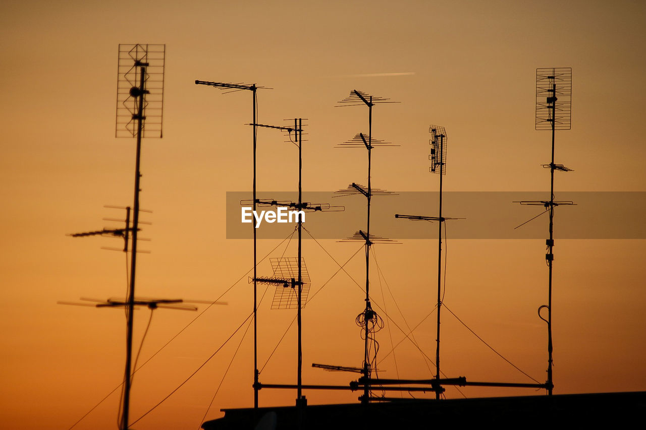 SILHOUETTE OF ELECTRICITY PYLONS AGAINST CLEAR SKY