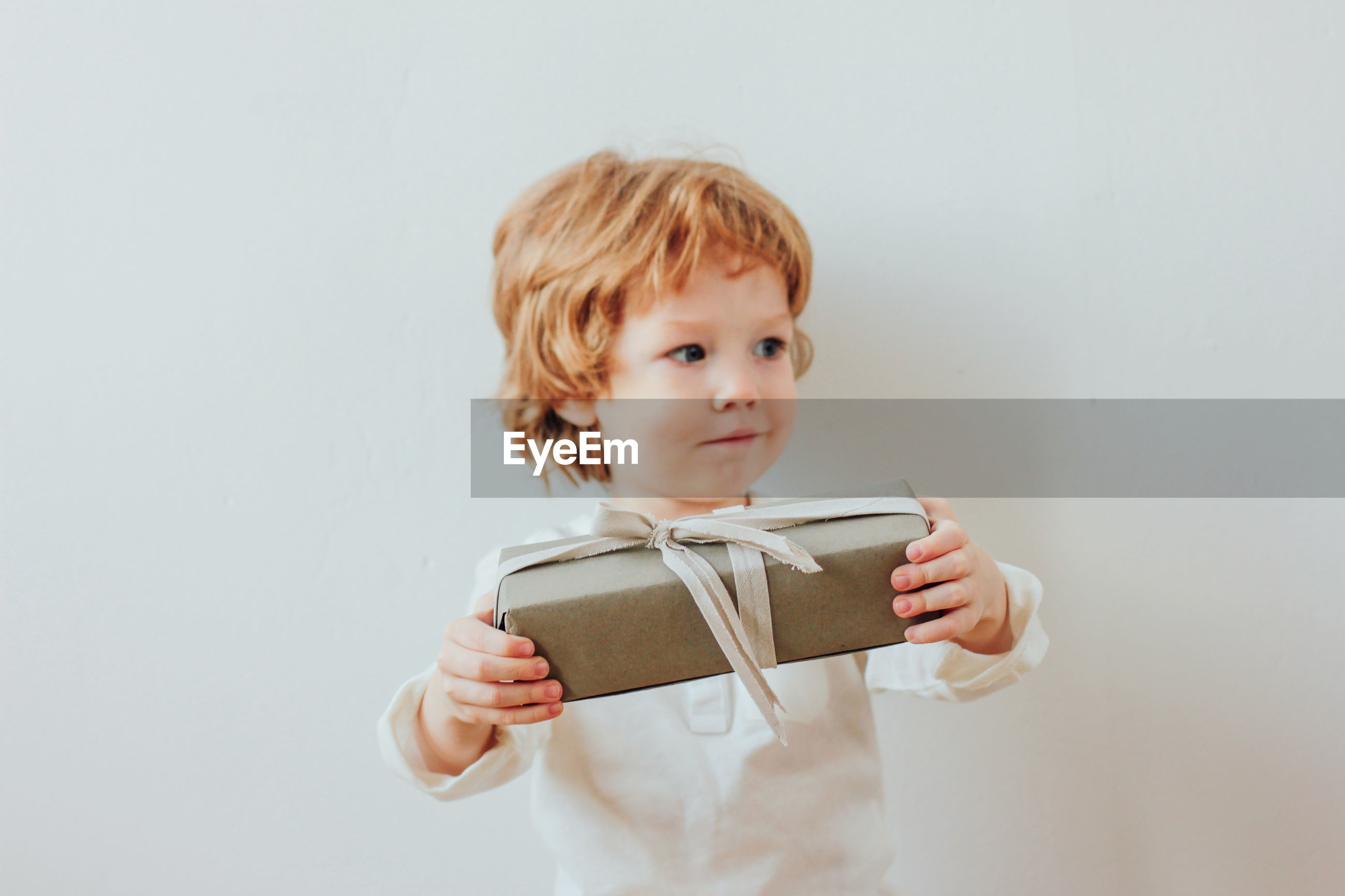 Boy holding christmas present against wall