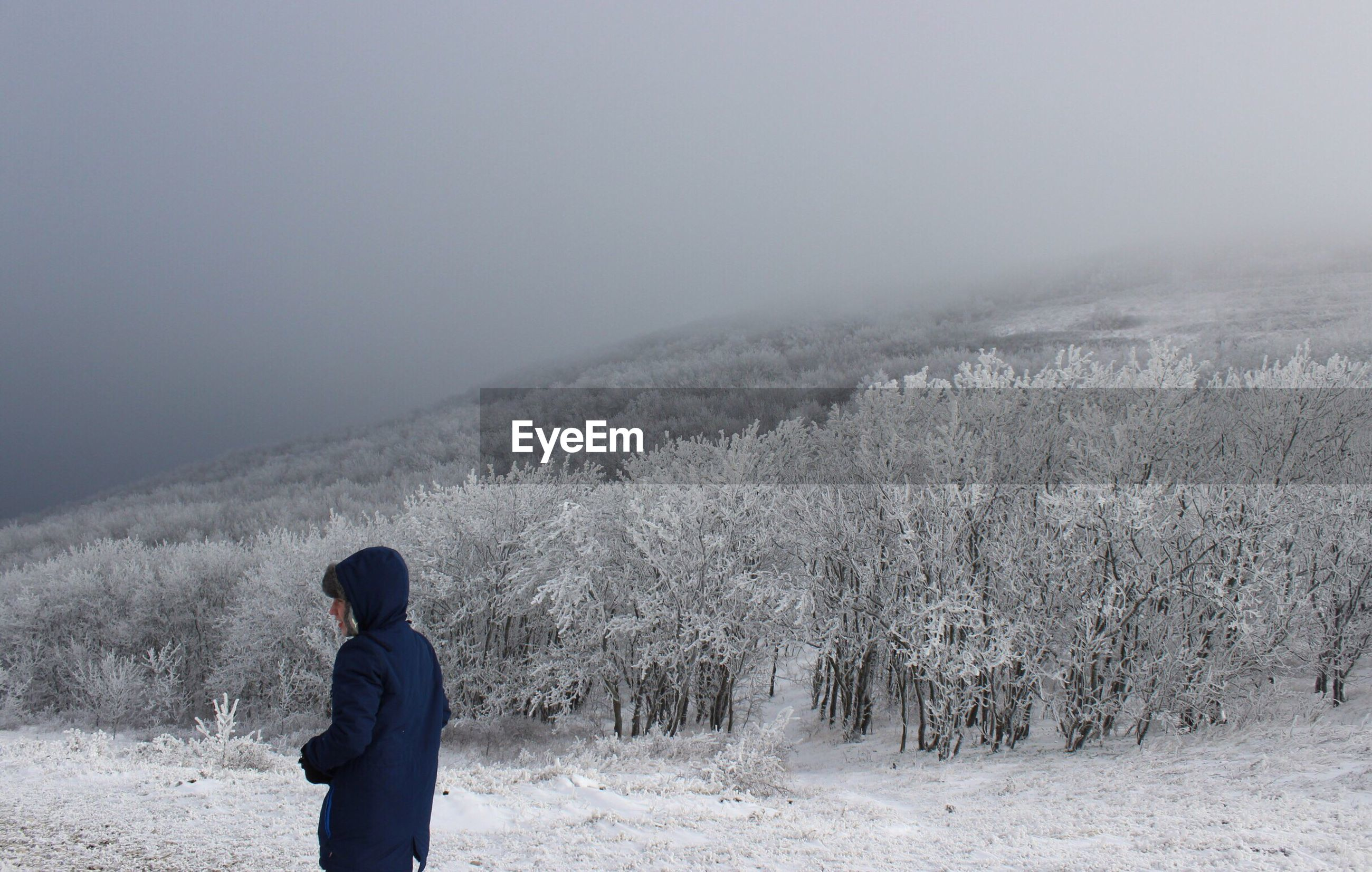 Rear view of person standing on snowy field during foggy weather