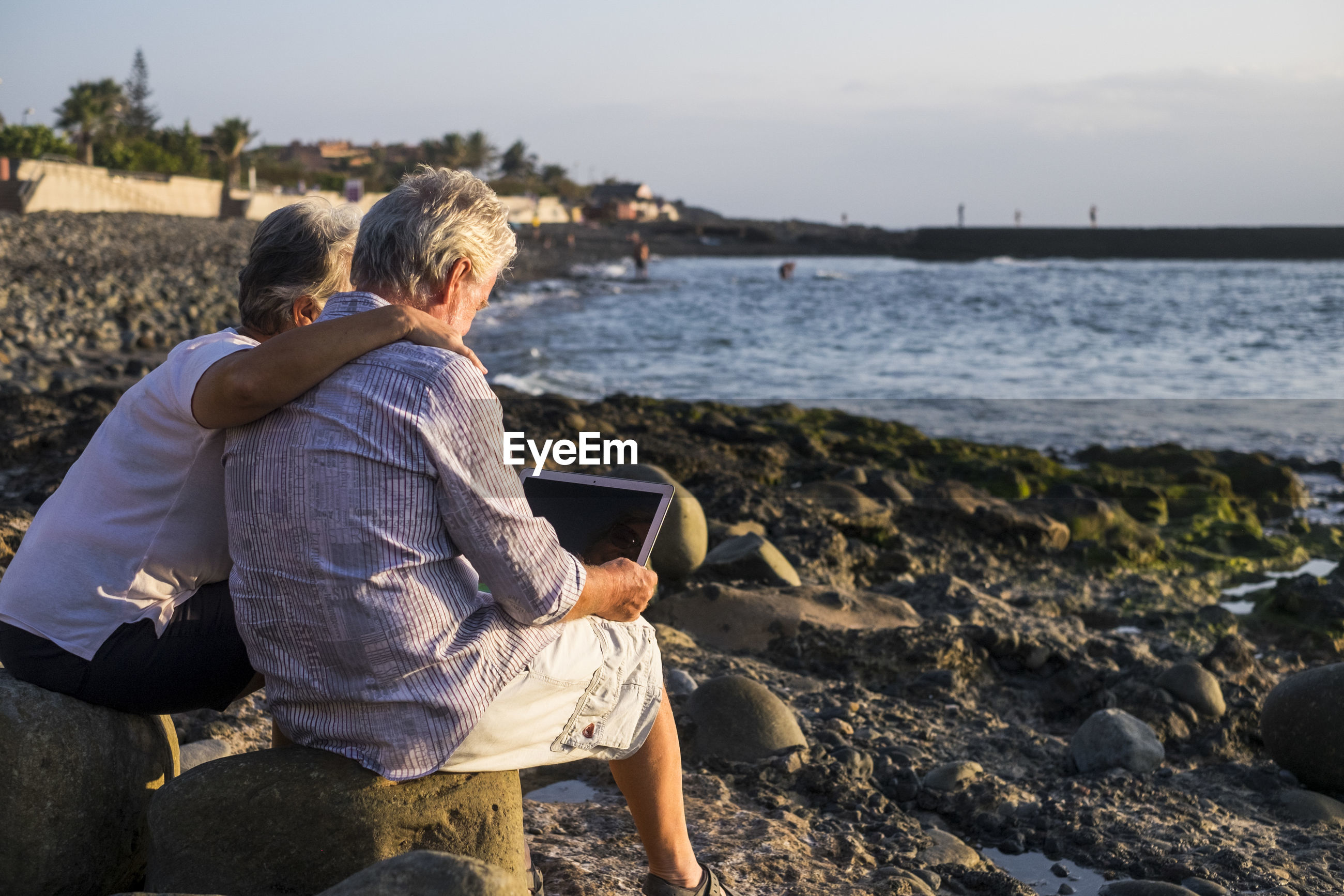 Senior man with woman using laptop while sitting on rock at beach