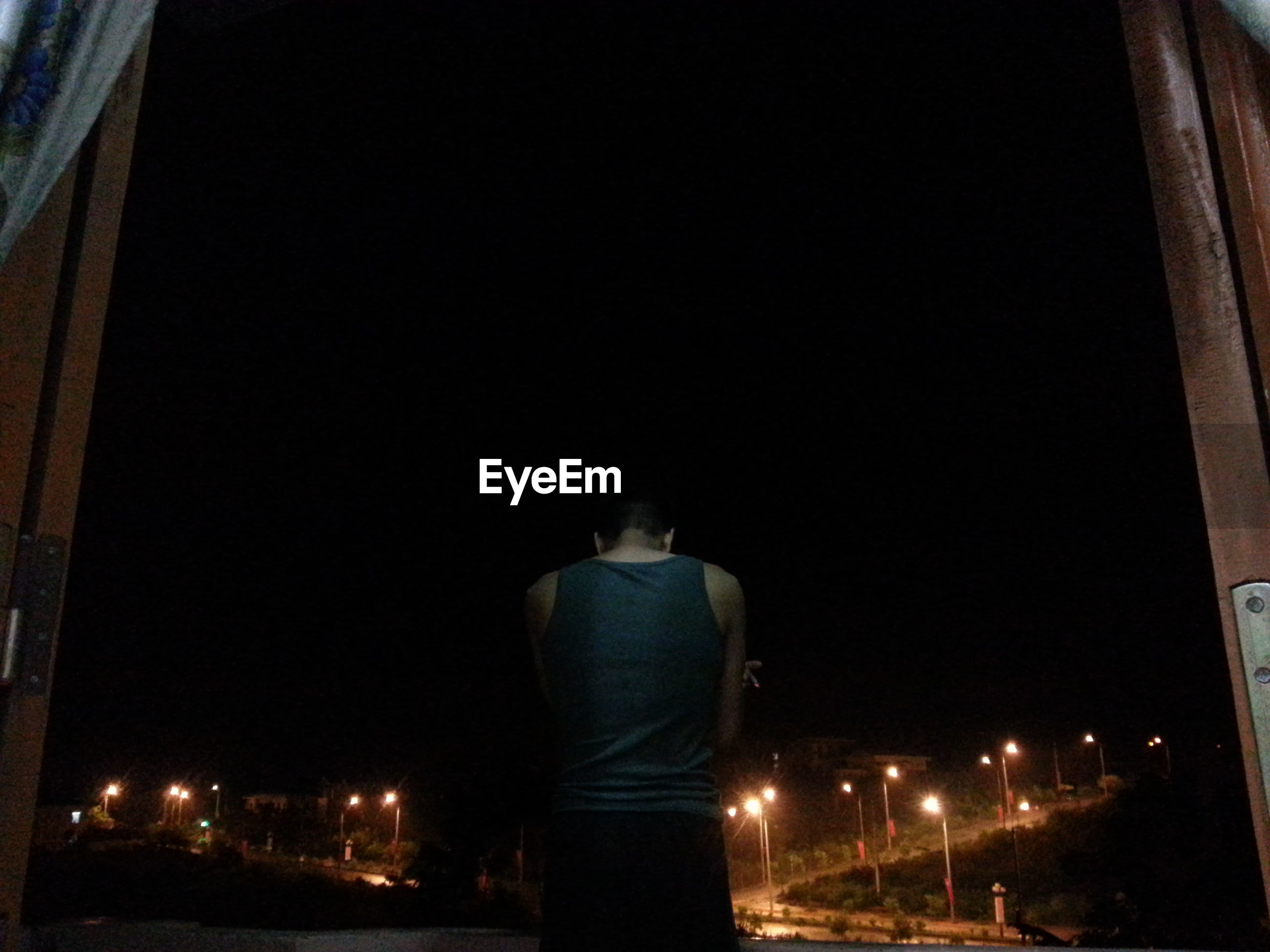 REAR VIEW OF MAN STANDING ON NIGHT