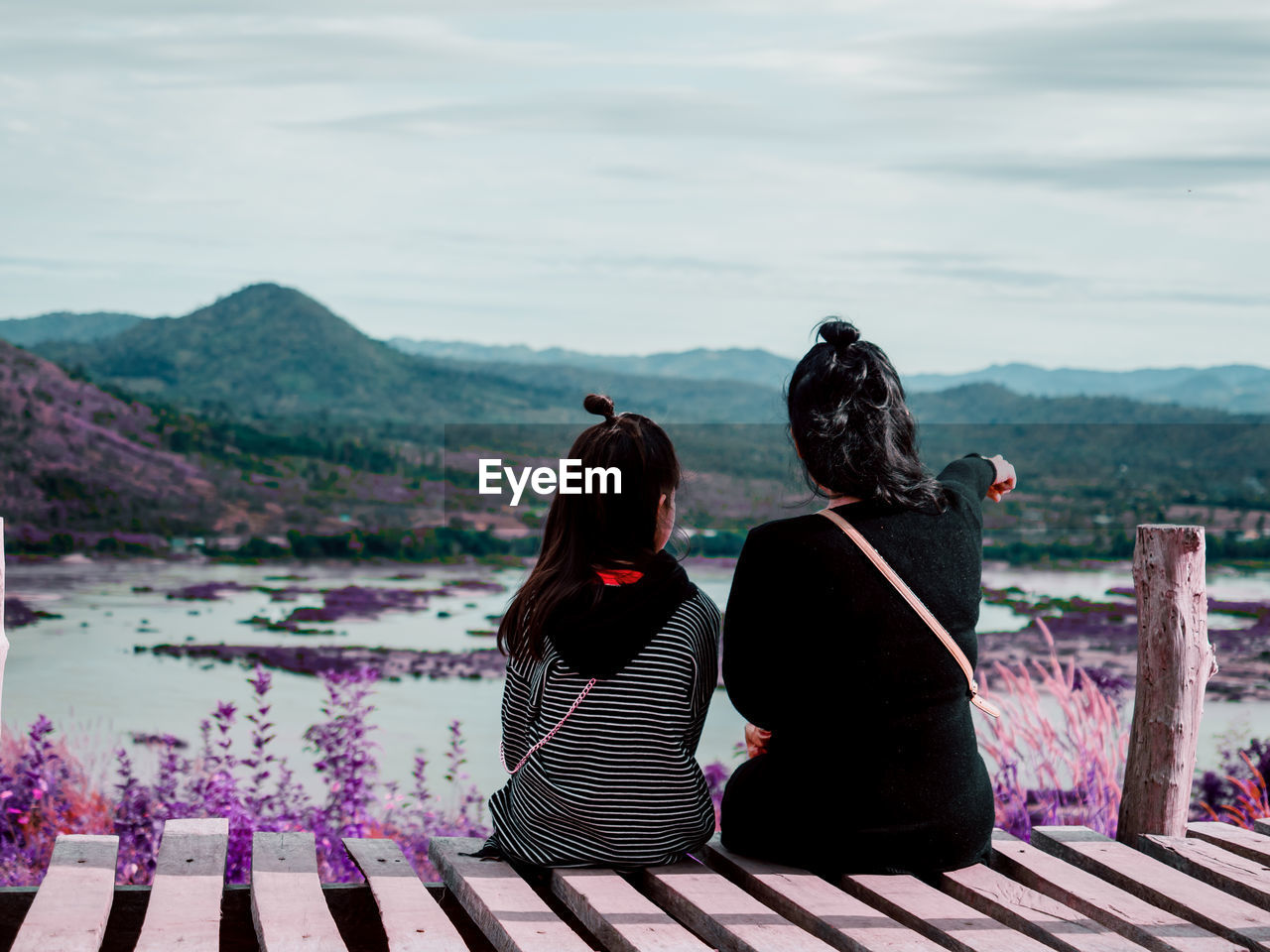Rear view of mother and daughter looking at landscape while sitting on boardwalk