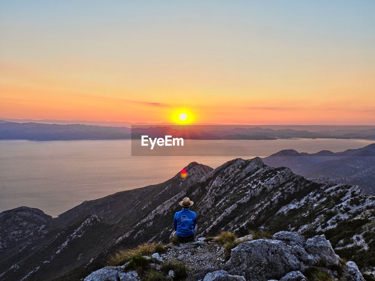 sunset, sky, beauty in nature, scenics - nature, leisure activity, real people, tranquility, mountain, lifestyles, tranquil scene, non-urban scene, orange color, sun, idyllic, rear view, one person, nature, rock, rock - object, solid, mountain range, outdoors