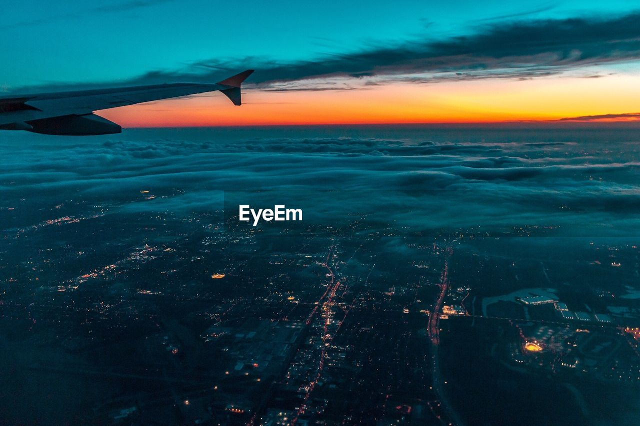 Airplane Flying Over City During Sunset