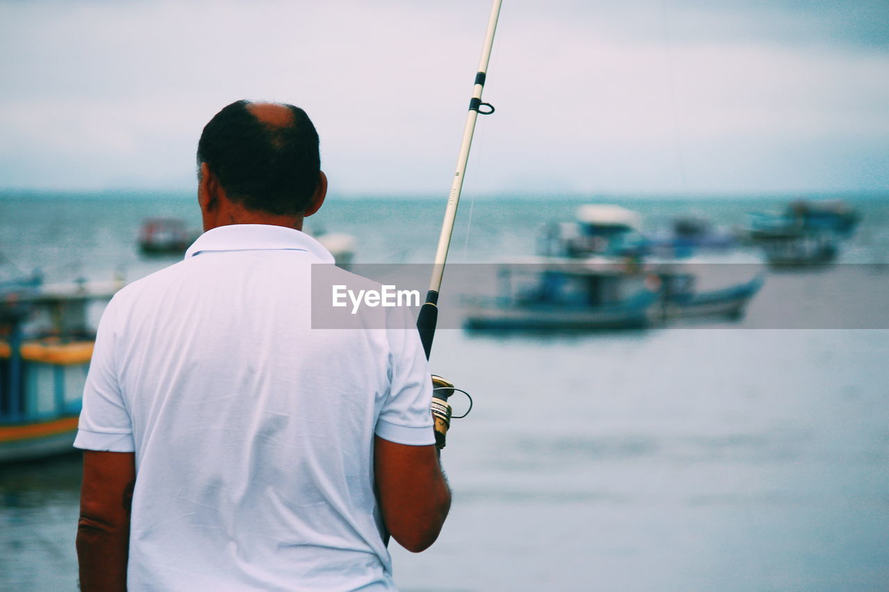 rear view, water, sea, real people, focus on foreground, one person, nature, men, nautical vessel, standing, sky, leisure activity, waist up, mode of transportation, day, transportation, lifestyles, holding, casual clothing, outdoors, sailboat
