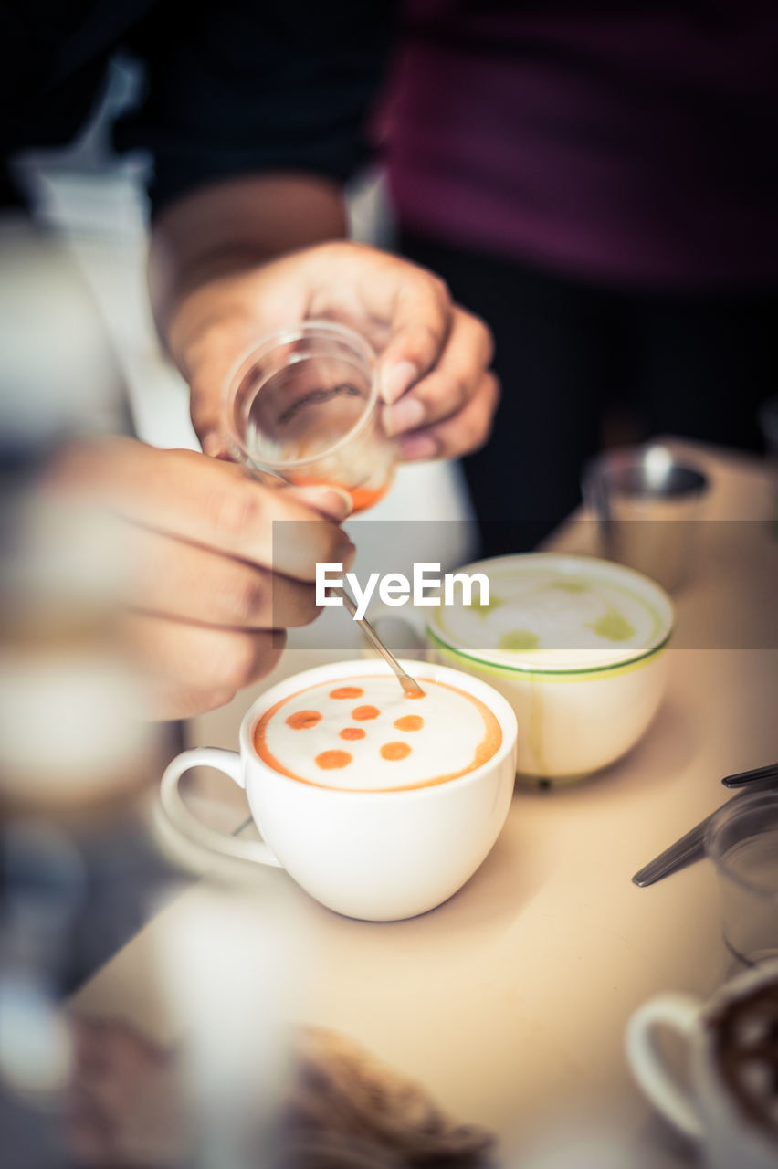High Angle View Of Barista Mixing Milk In Drink At Cafe