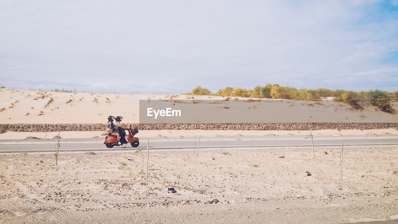 Man And Woman Riding On Scooter In Barren Landscape