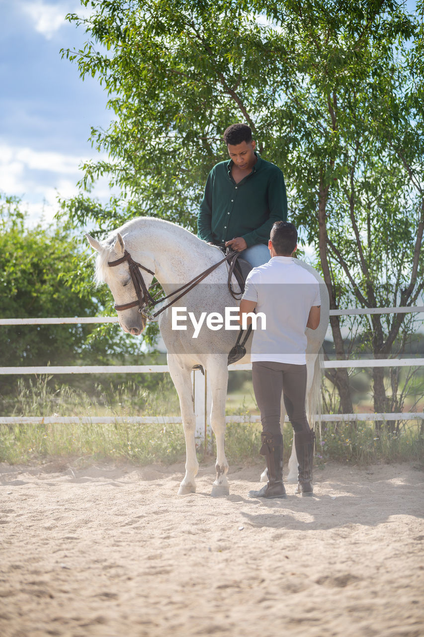 Man standing by friend sitting on horse in pen