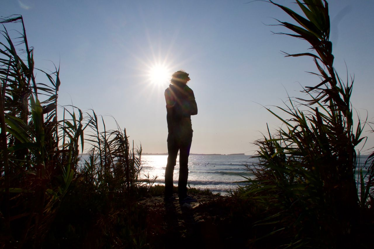 sky, nature, plant, sunlight, beauty in nature, standing, water, one person, sun, lens flare, sunbeam, growth, leisure activity, real people, scenics - nature, sea, men, non-urban scene, outdoors, bright