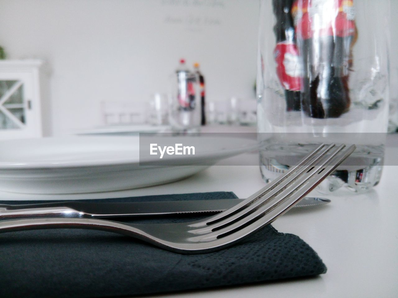 Close-up of fork and knife by plate on table