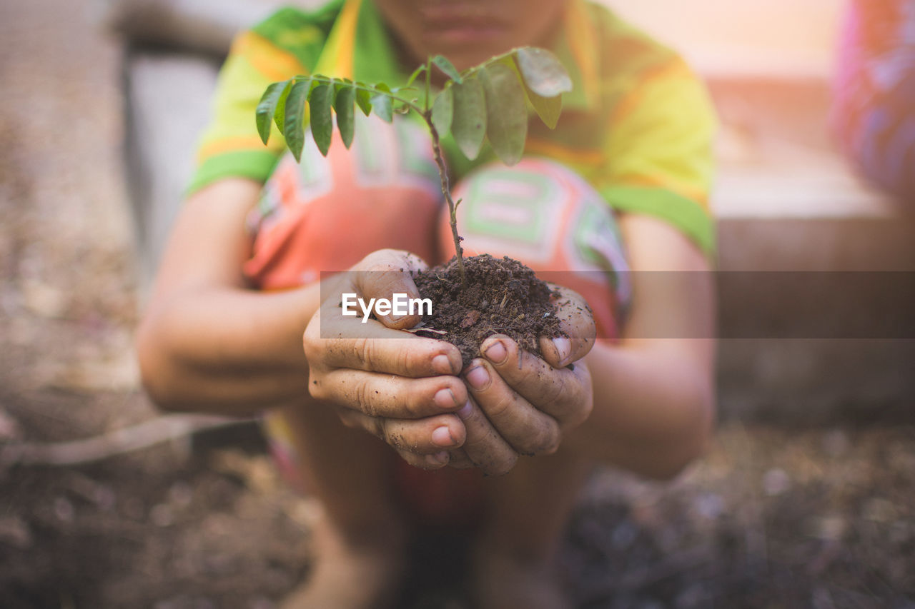 Midsection of child planting in garden
