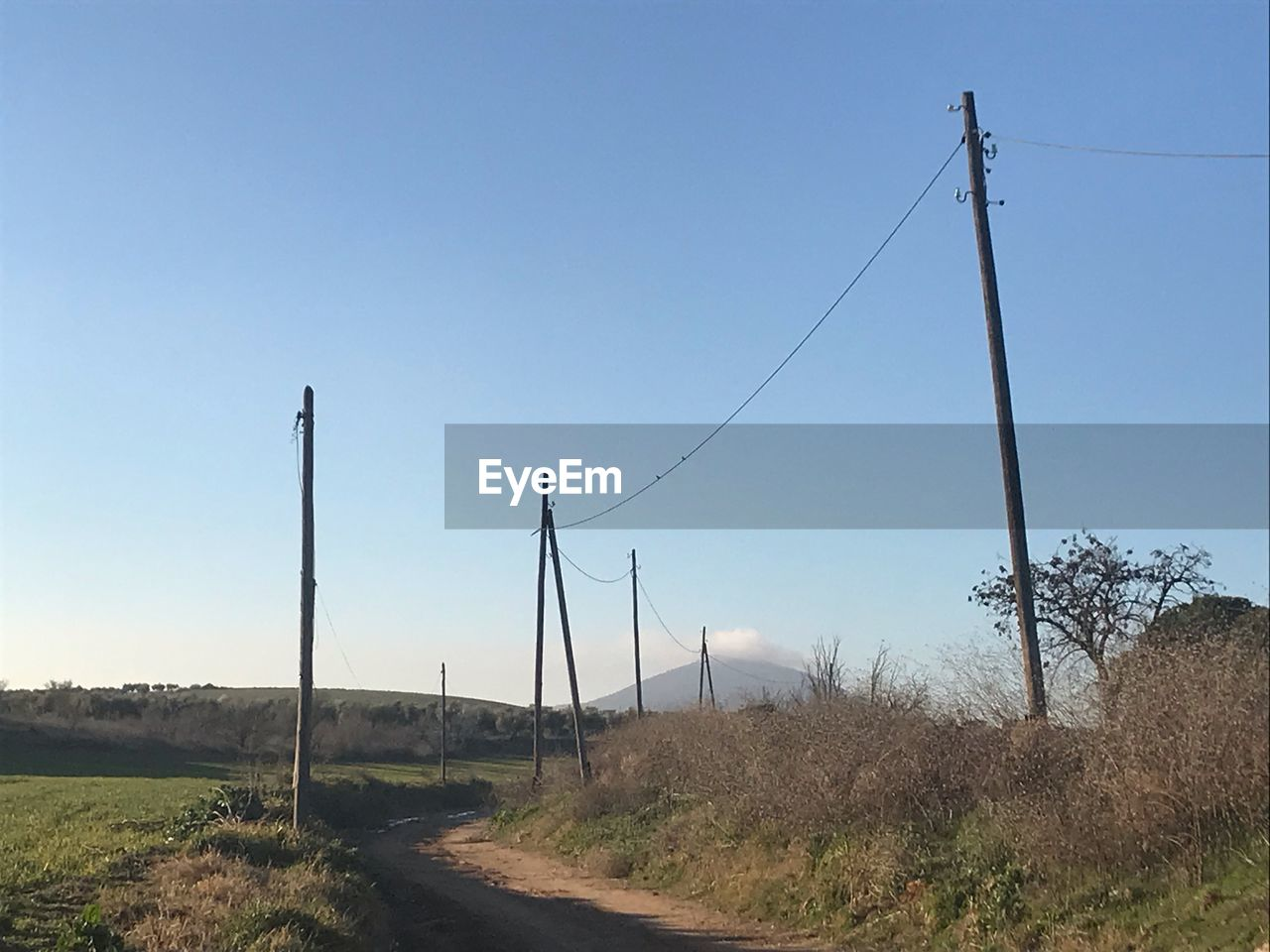 sky, electricity, landscape, clear sky, technology, cable, land, no people, road, nature, field, connection, plant, electricity pylon, environment, pole, day, power line, grass, tranquility, outdoors, power supply, telephone line