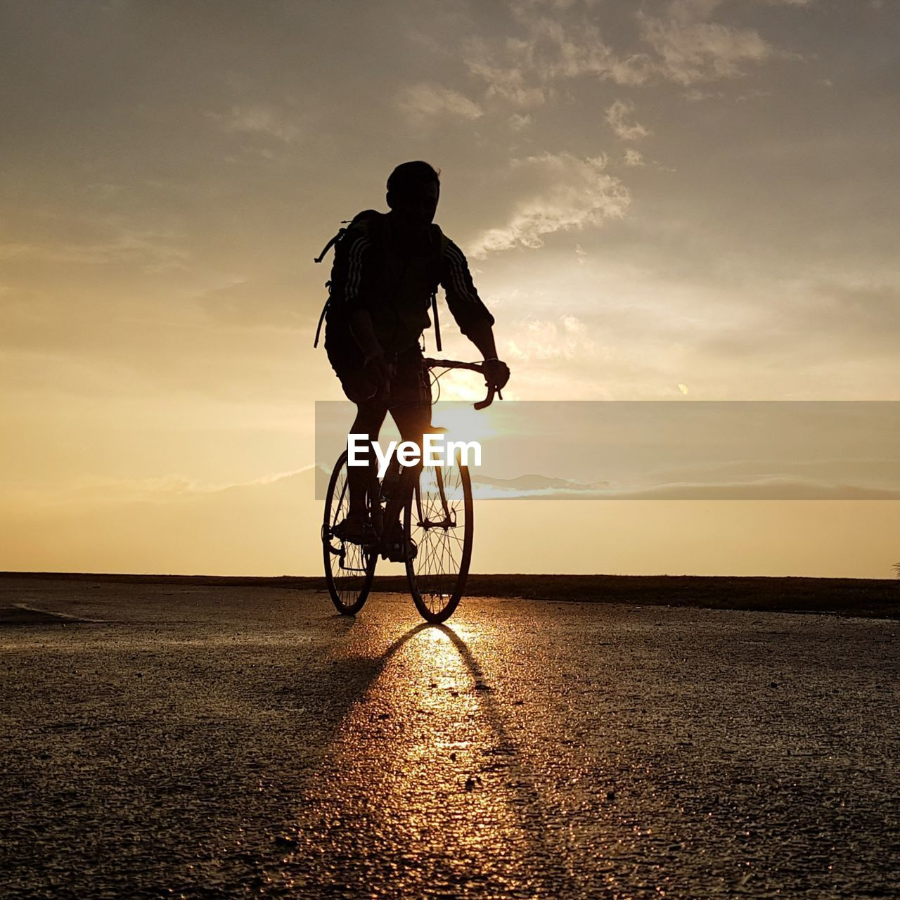 Silhouette Man Riding Bicycle At Beach During Sunset
