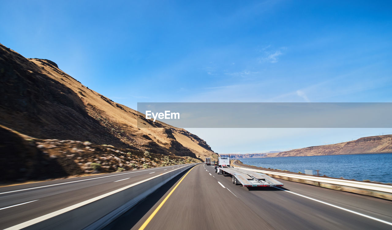 transportation, road, sky, mountain, mode of transportation, motor vehicle, car, land vehicle, nature, the way forward, motion, road marking, day, no people, direction, scenics - nature, marking, symbol, beauty in nature, mountain range, outdoors, diminishing perspective, formation, dividing line