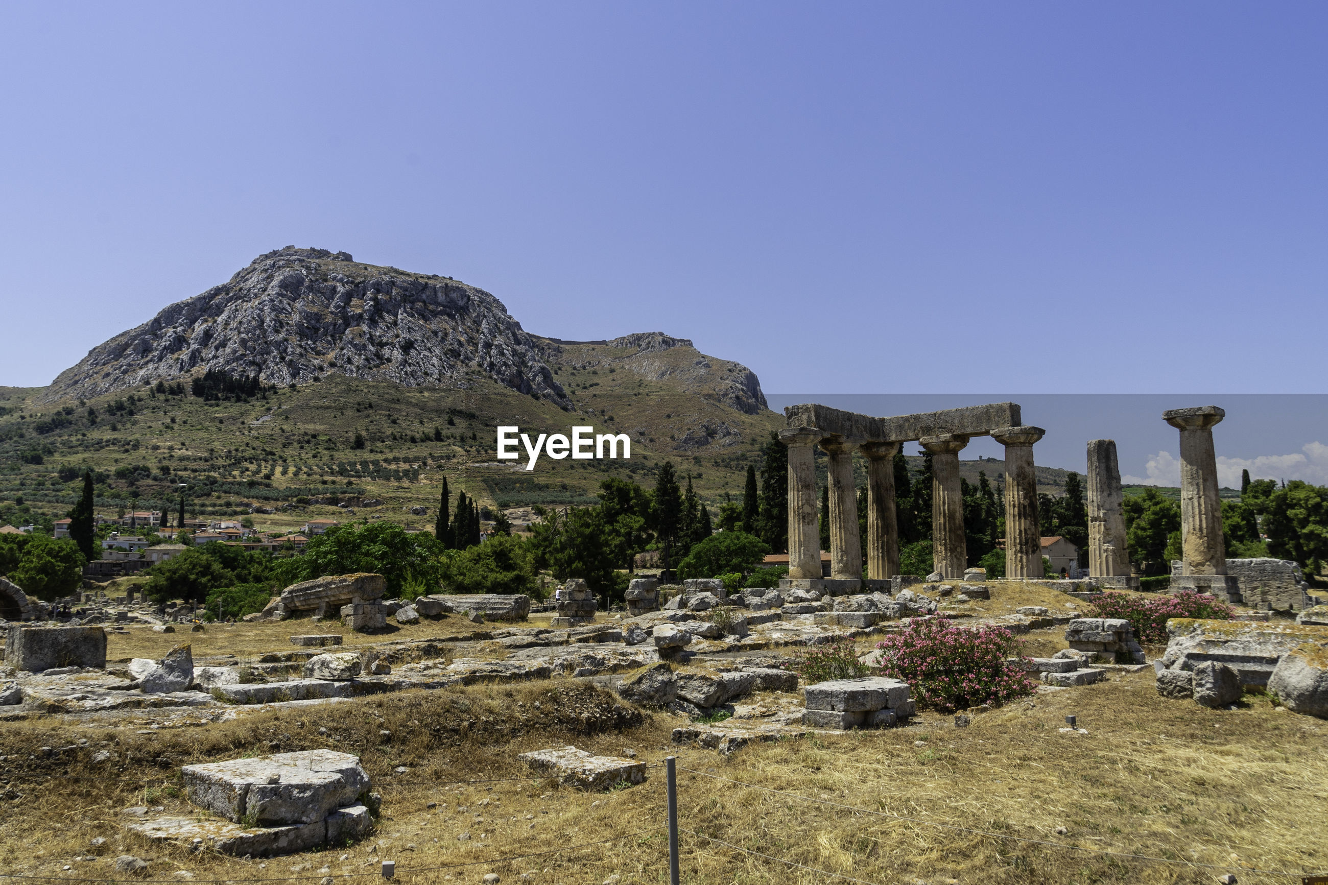 Ruins of ancient apollo temple in front of acrocorinth in front of blue sky