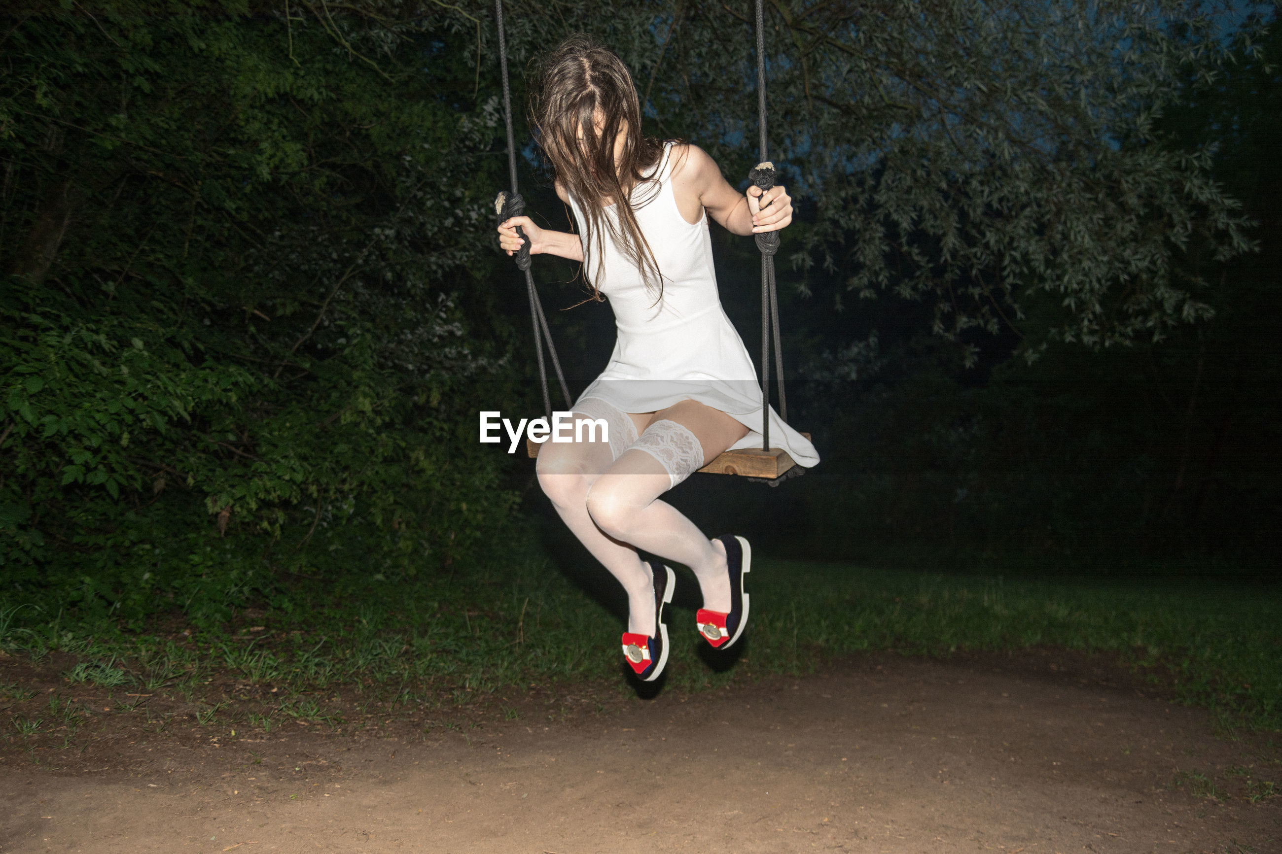 Full length of woman sitting on swing at park