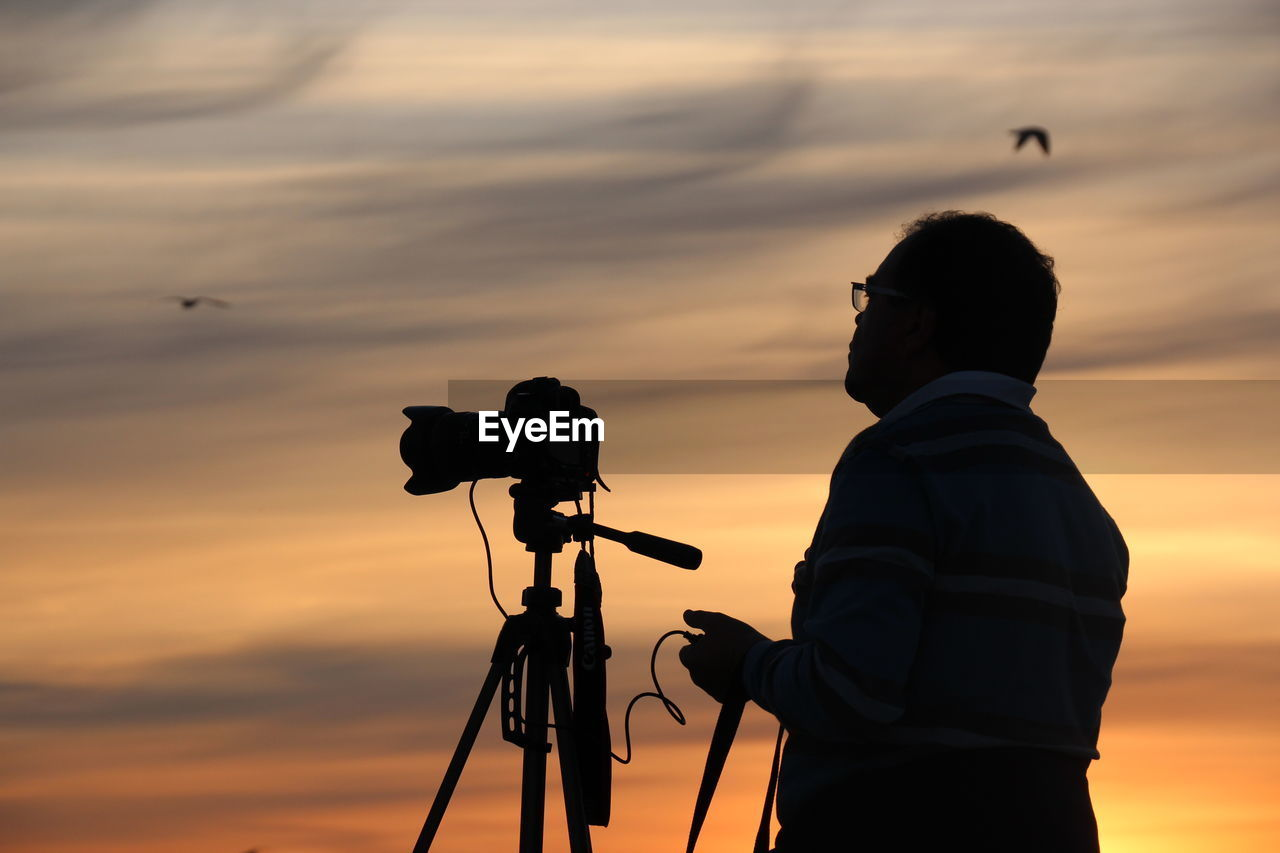 Rear View Of Man With Camera Against Sky During Sunset