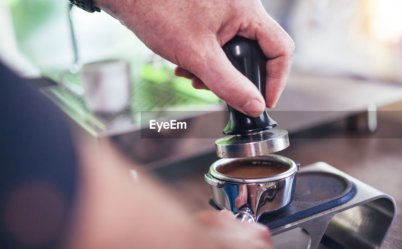 human hand, hand, real people, human body part, one person, selective focus, holding, indoors, close-up, human finger, finger, men, unrecognizable person, lifestyles, metal, body part, focus on foreground, coffee maker, equipment