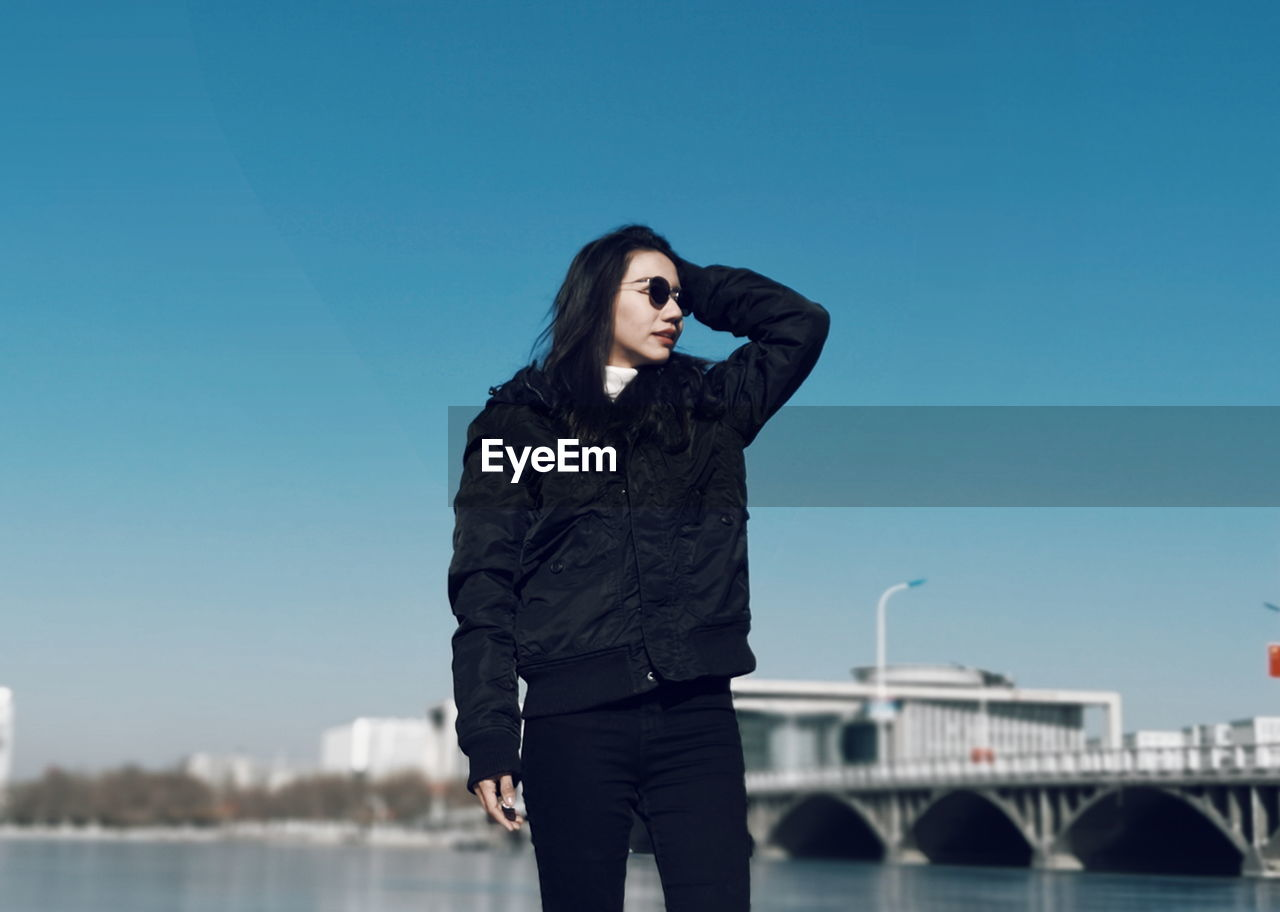 Woman wearing jacket standing by river against blue sky