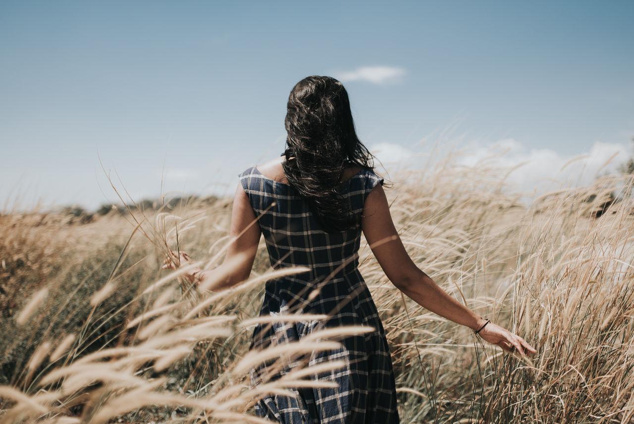 Rear View Of Woman Walking On Grassy Field Against Sky