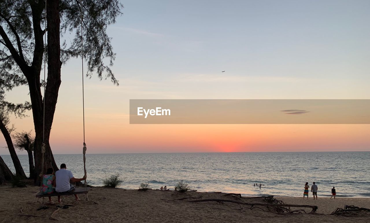sky, water, sea, sunset, land, beach, beauty in nature, real people, scenics - nature, horizon over water, horizon, leisure activity, tree, men, nature, tranquility, tranquil scene, lifestyles, sitting, outdoors