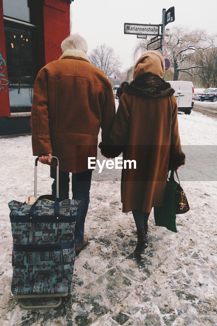 Two people walking with luggage in winter