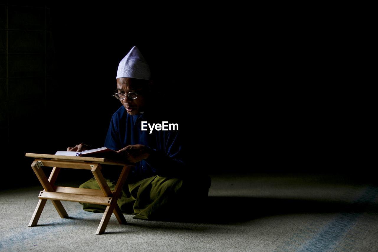 Man Reading In Koran In Mosque