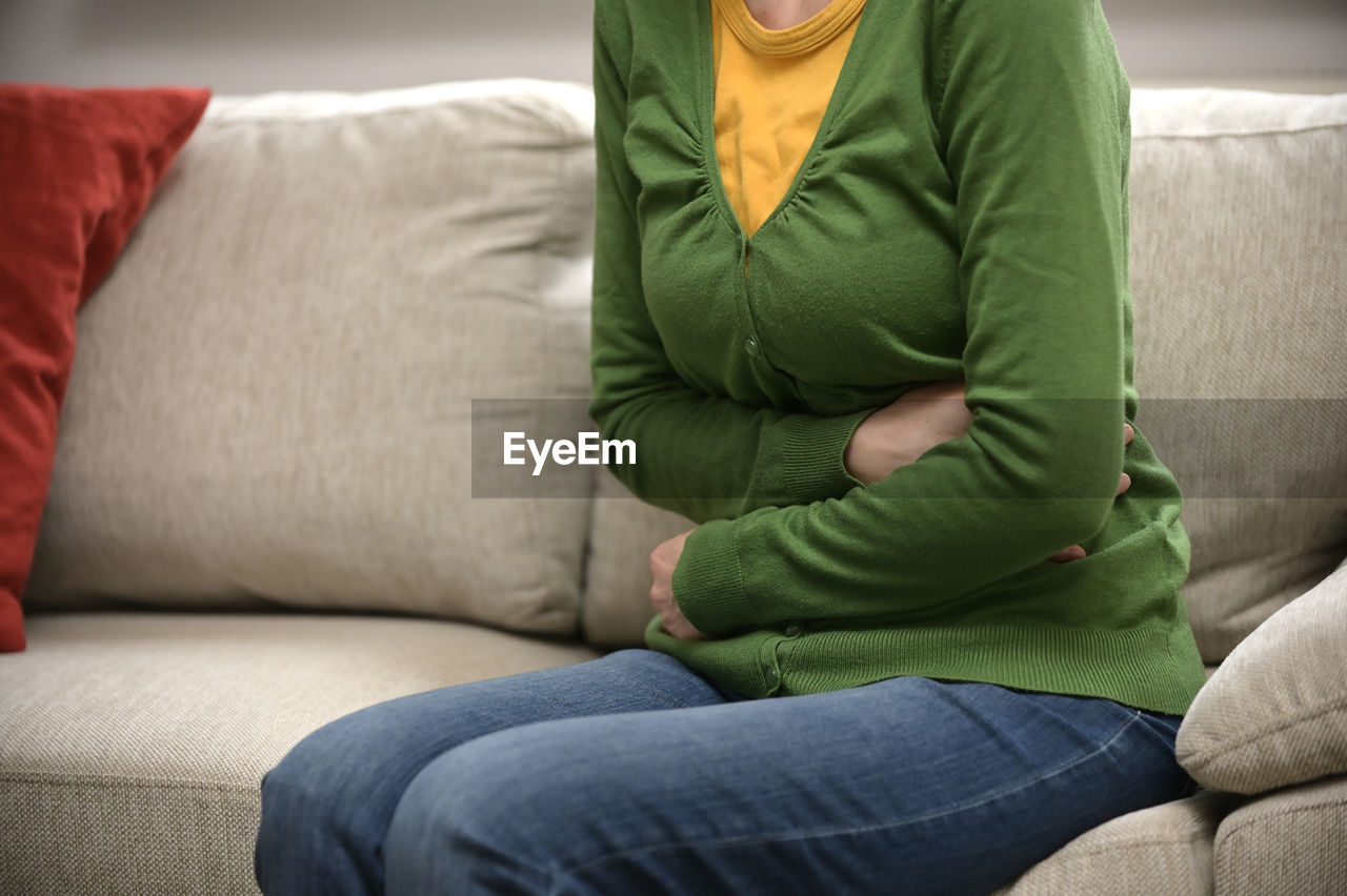 Midsection of woman suffering from stomached sitting on sofa at home
