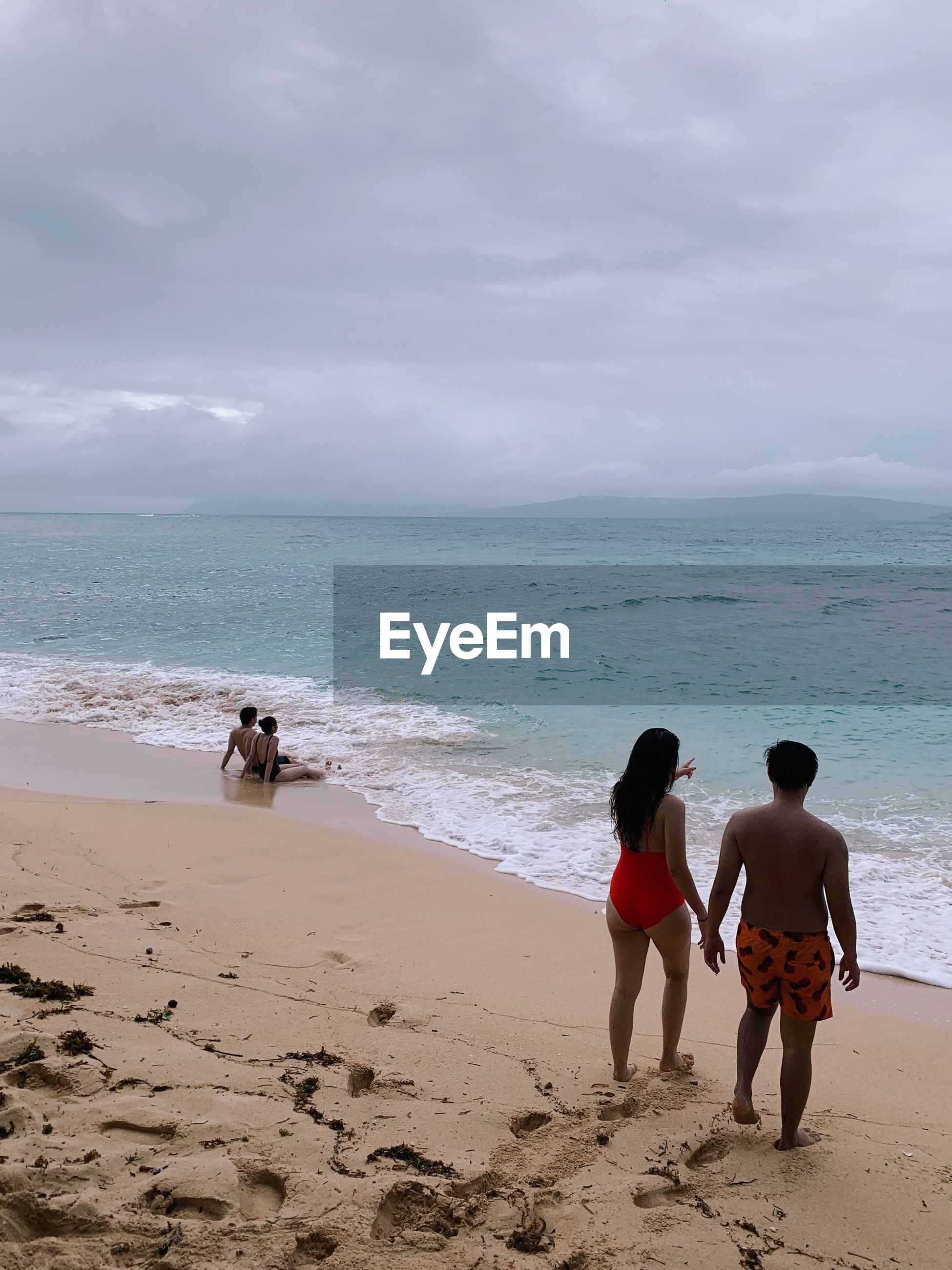 High angle view of couple holding hands while standing on shore at beach against sky