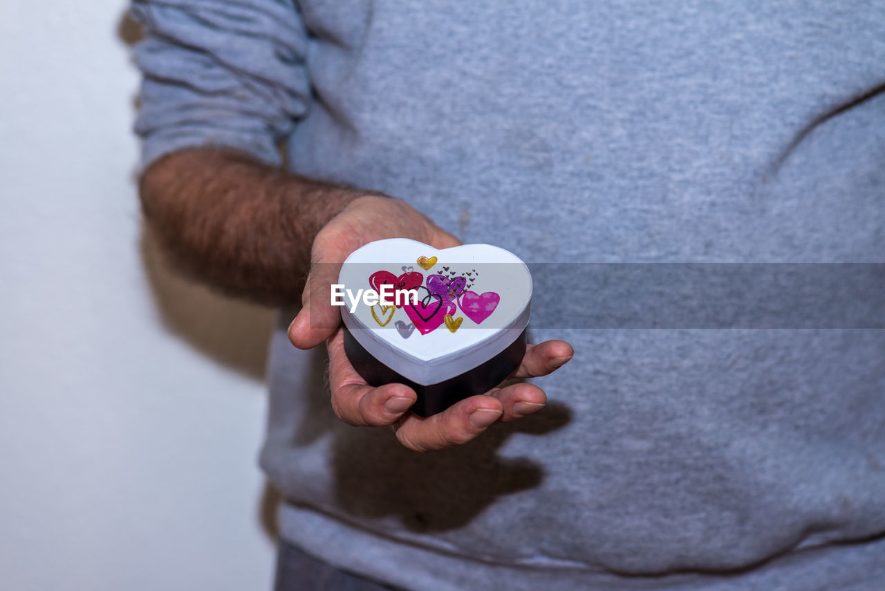 Midsection of man holding heart shape container
