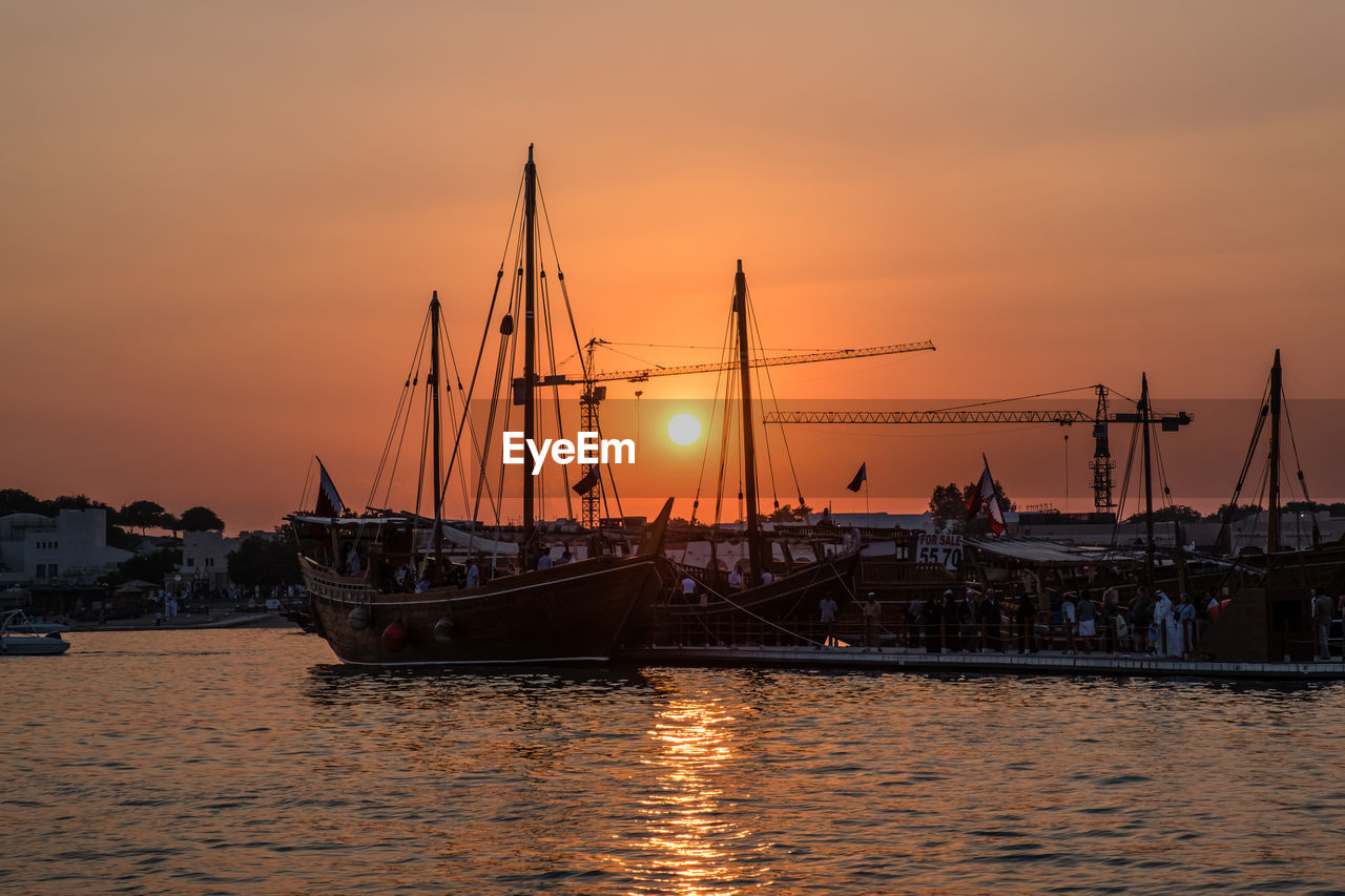 sunset, nautical vessel, transportation, sky, water, mode of transportation, orange color, sea, sailboat, mast, waterfront, no people, nature, harbor, pole, moored, sun, beauty in nature, scenics - nature, outdoors, marina, yacht, bay