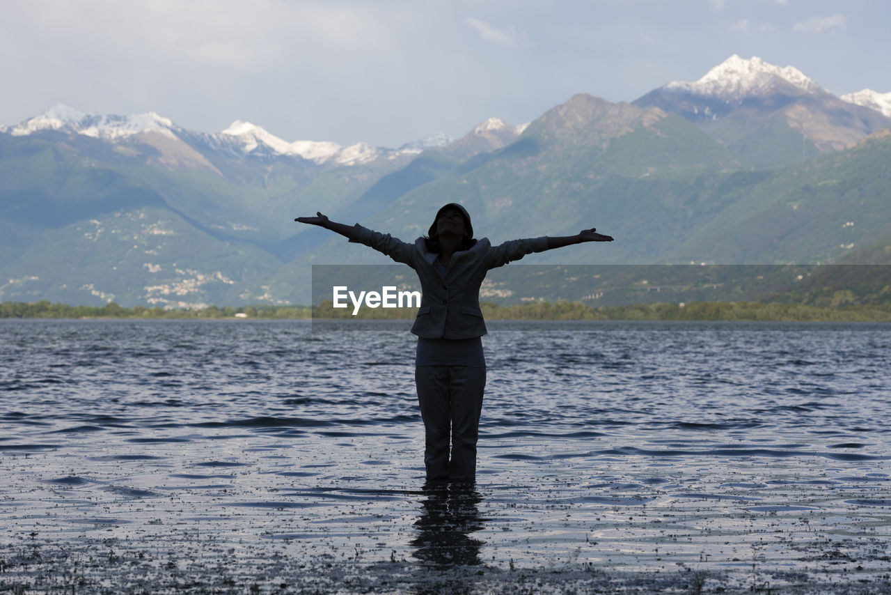 Woman Standing With Arms Outstretched In Lake Maggiore Against Mountains