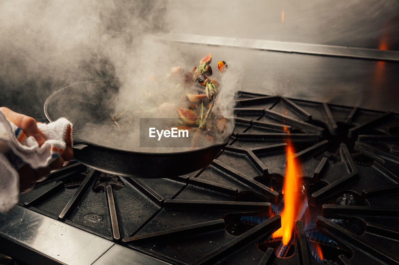 Cropped hand tossing vegetables in cooking pan over stove in kitchen at home