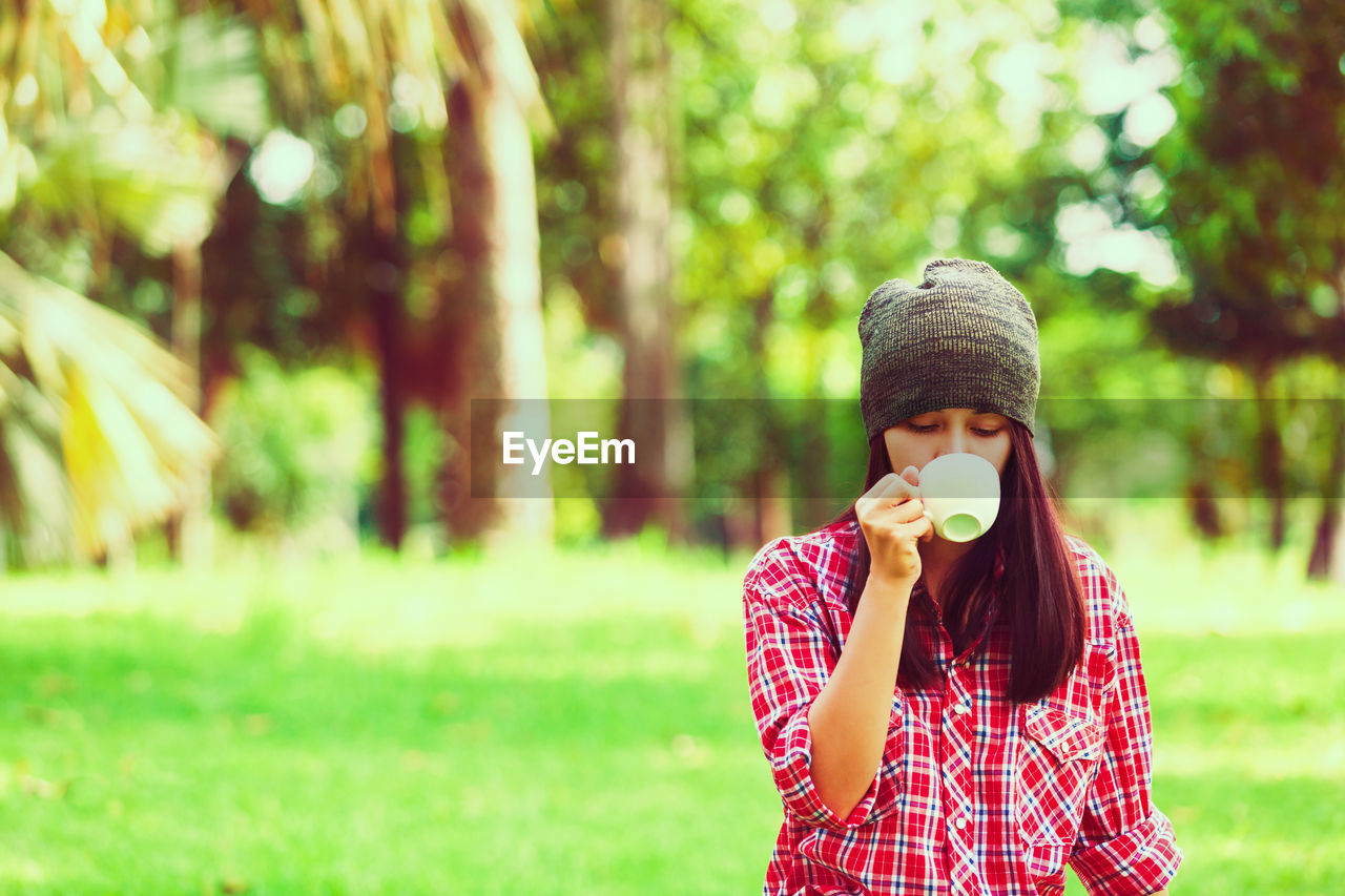 Young woman drinking coffee on field