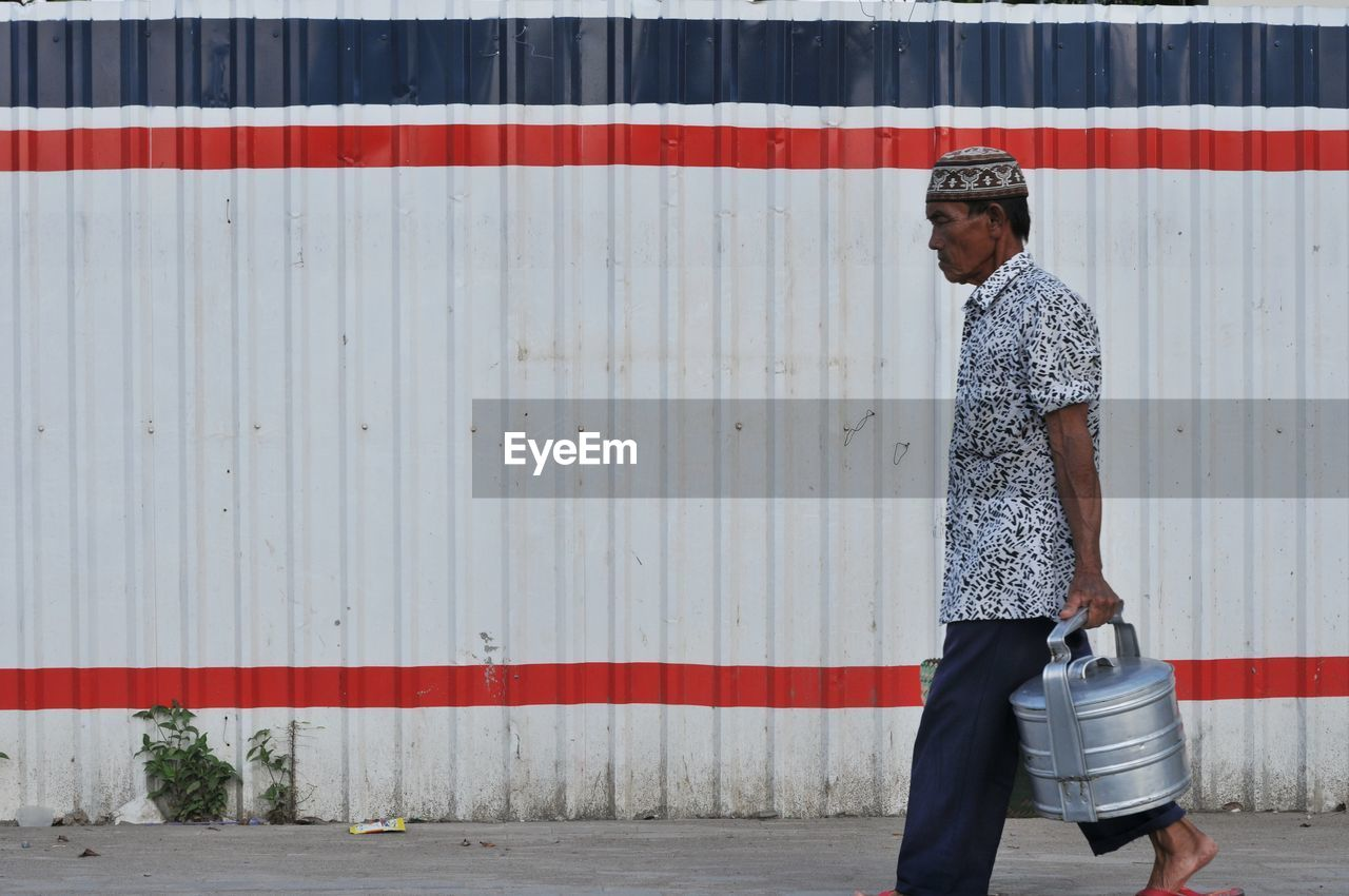 Side view of man with containers walking on footpath
